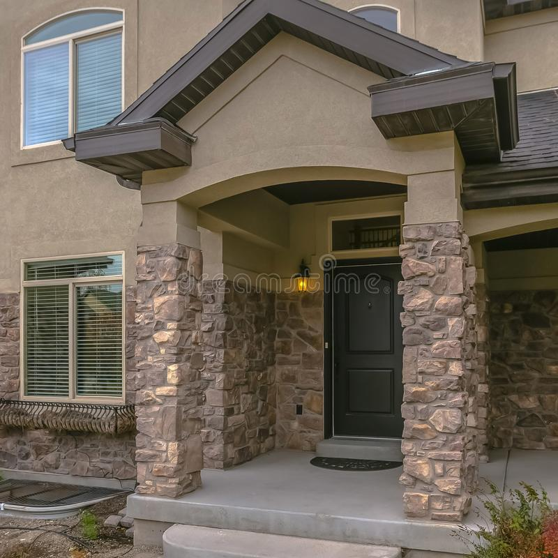 Square frame Facade of a home with stone wall and welcoming covered front porch stock photos