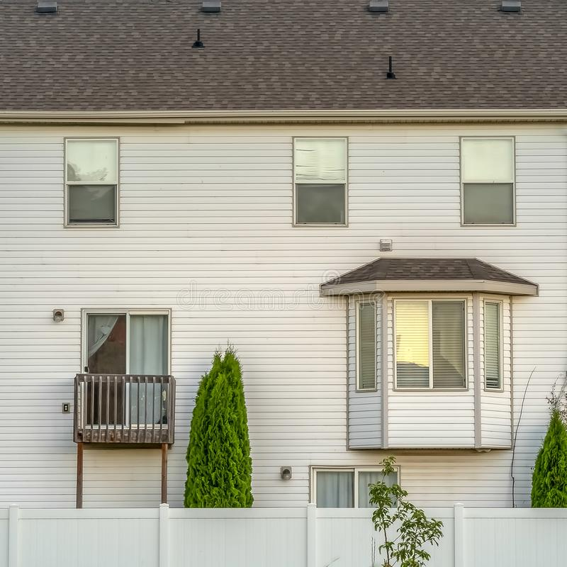 Square frame Facade of home with white wall bay window small balcony and wooden fence stock photo