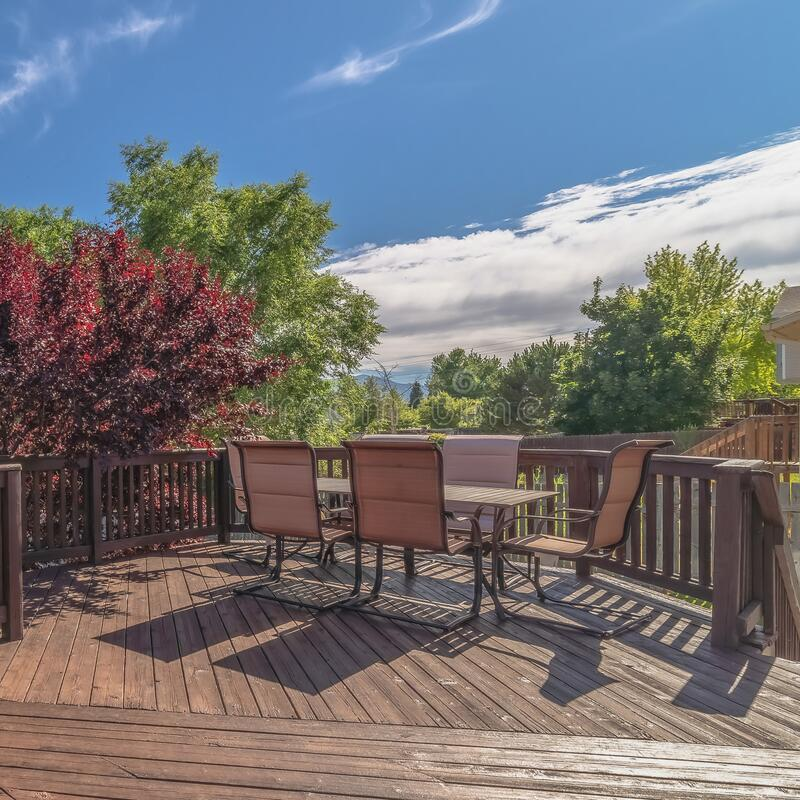 Square frame Furniture on the balcony of home with brown wooden floor railing and stairs. The outdoor living space has a scenic view of the yard, trees, and stock photography