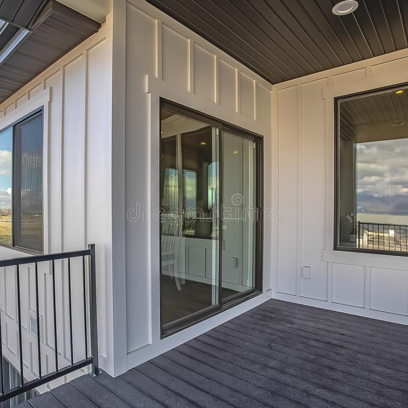 Square frame Home balcony with wooden floor metal railing and sliding glass access door. The scenic outdoor view is reflected on the shiny windows royalty free stock image
