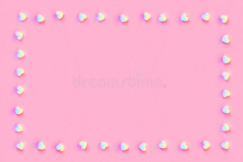Square frame made of small white sugar candy hearts on a pastel living coral color paper stock photography