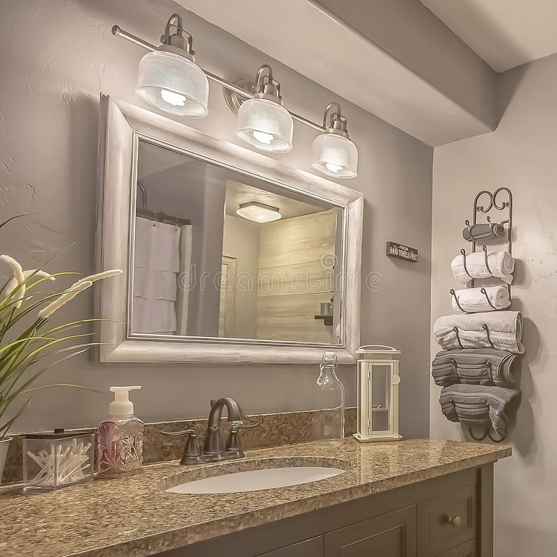 Square frame Mirror and lamps above the vanity inside a bathroom with towel rack and shelves. A white curtain conceals the bathtub and shower area royalty free stock photography