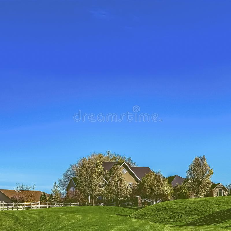 Square frame Narrow paved road on a vast grassy terrain under blue sky on a sunny day. The pathway leads to the houses on a residential area in the distance royalty free stock photos