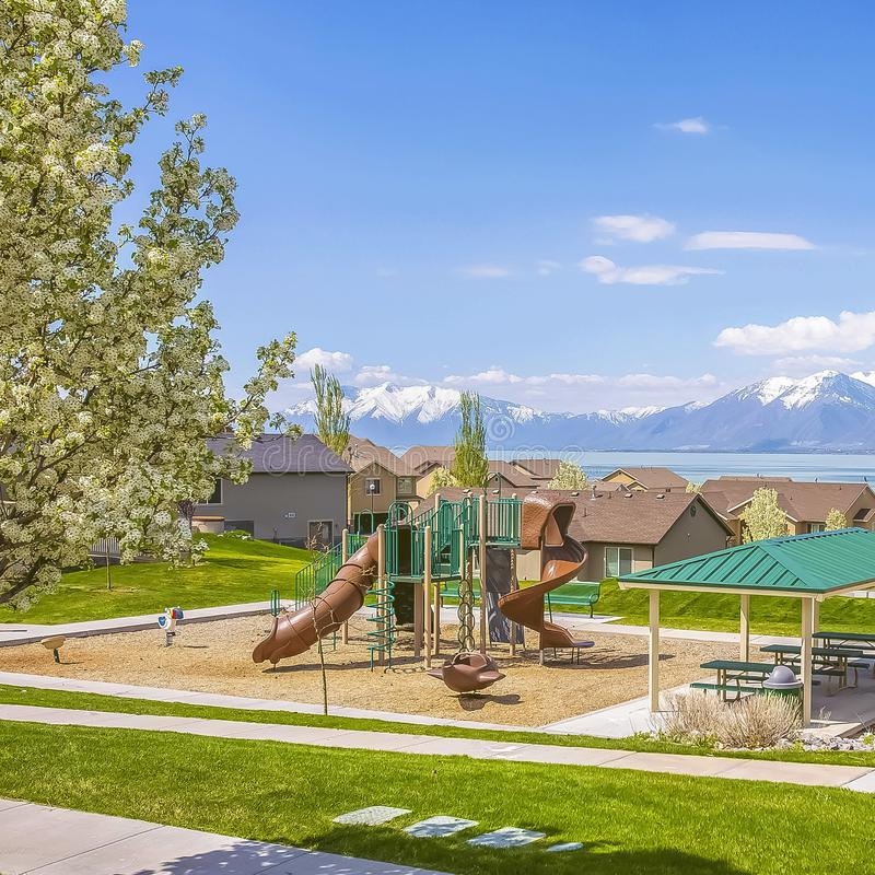 Square frame Playground and homes overlooking a lake and snowy mountain against blue sky. Grassy terrain with pathways and white flowering tree cna be seen in royalty free stock images