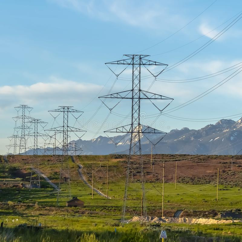 Square frame Power lines towering over neighborhood and roads in the valley on a sunny day. Blue sky and mountain with snowy peaks cna be seen in the stock photos