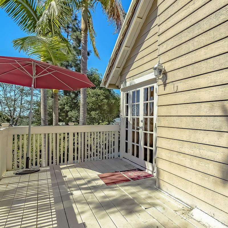 Square frame Red umbrella at the corner of the balcony of a house with wooden exterior wall. Lush trees can be seen against the clear blue sky on this sunny stock image