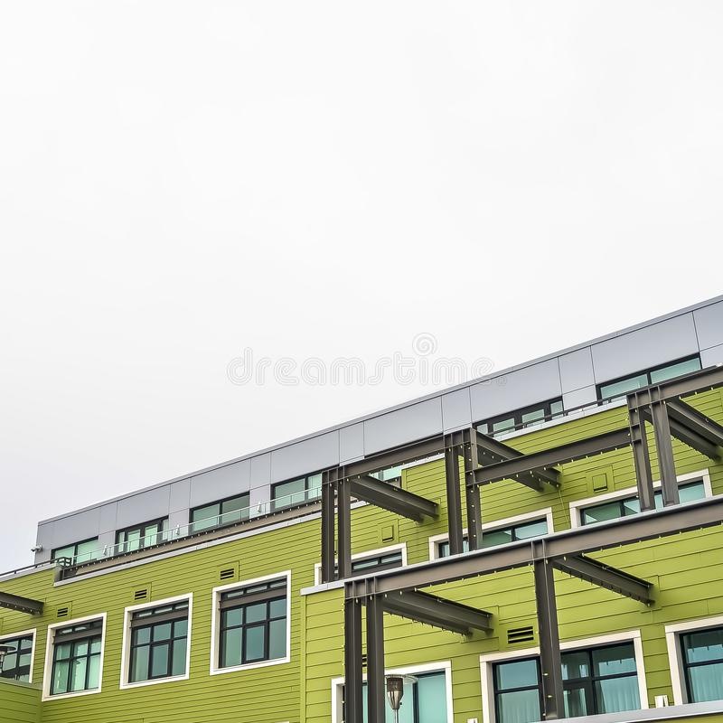 Square frame Residential building exterior with green horizontal siding and flat roof royalty free stock photography