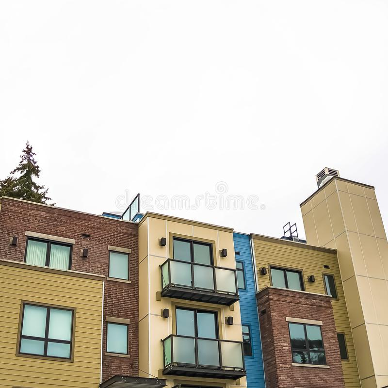 Square frame Residential building facade with flat roof and balconies with glass railings stock photography