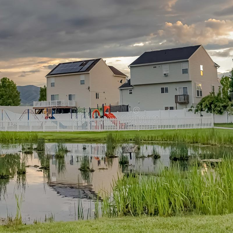 Square frame Shiny pond playground and multi storey homes surrounded by vast grassy terrain. Over the landscape is a sky filled with gray clouds at sunset stock images
