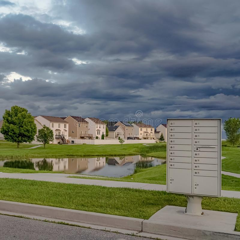 Square frame Sky filled with gray clouds over homes and pond amid a vast grassy terrain. White metal cluster mailbox at the side of a road can be seen in the stock images