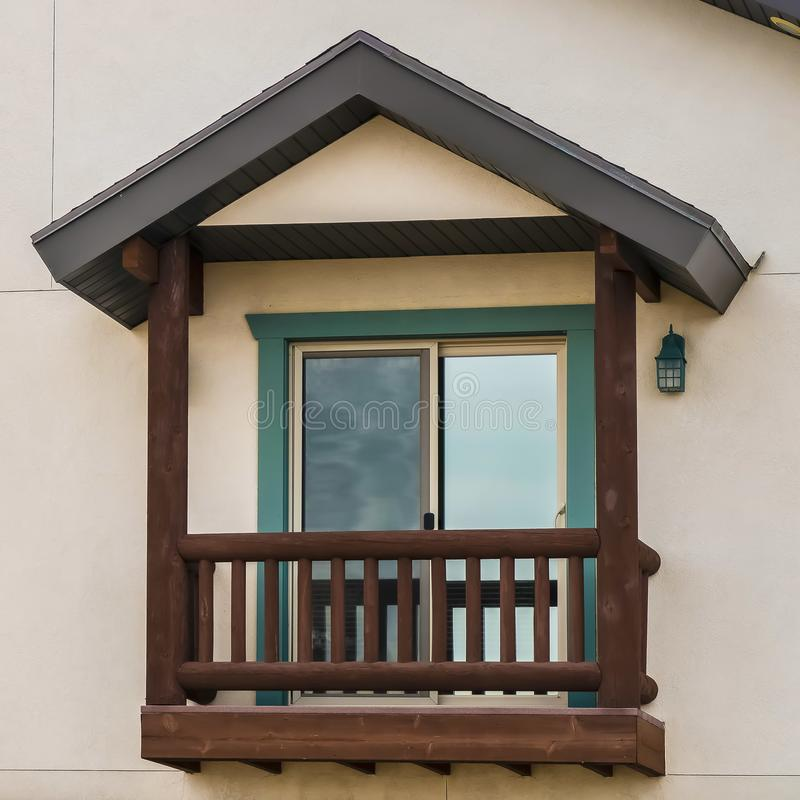 Square frame Small balcony with brown wooden railings and posts under a pitched roof. A shiny sliding glass door leads to the interior of this house royalty free stock photography