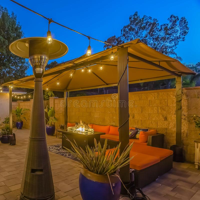 Square frame Stone brick patio of a home illuminated with string lights and lamp posts. The open air dining area is under an umbrella while the seating area is royalty free stock photos