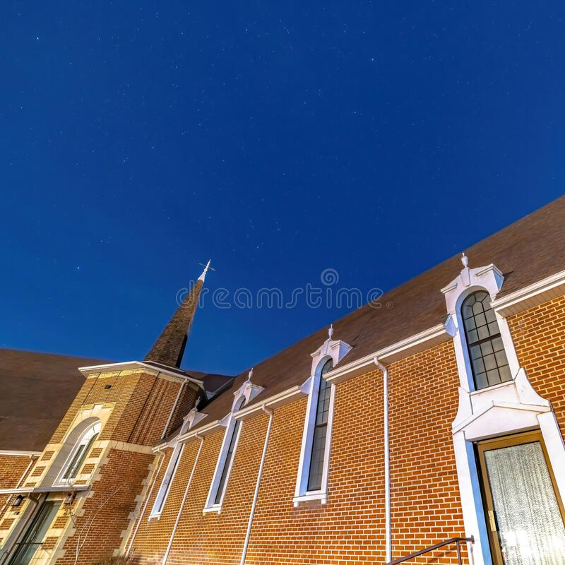 Square frame Vivid blue sky over a church in Provo Utah with brick wall and arched windows. The religious building also features a steeple and glass door at stock photography
