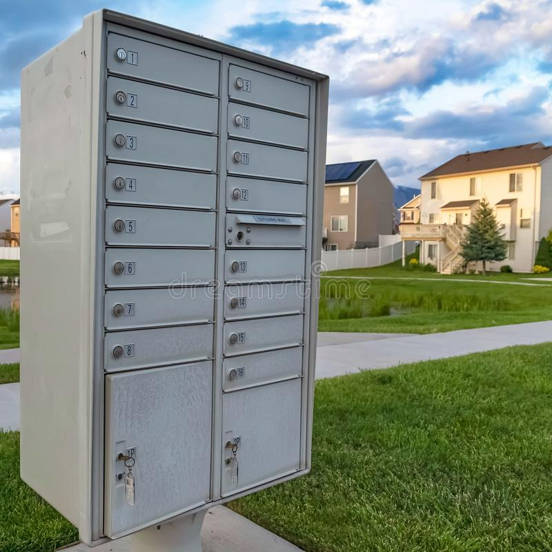Square frame White metal cluster mailbox with pond grassy terrain and homes in the background. Cloudy sky and snow capped mountain can also be seen in this stock photography
