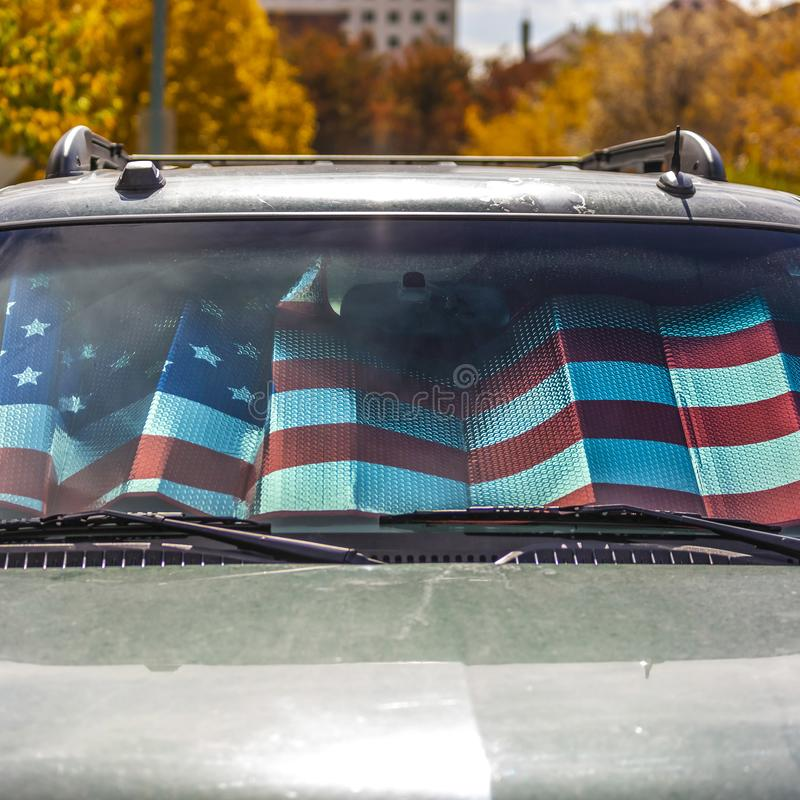 Square Front view of a shiny gray vehicle against lush trees on a sunny autumn day. Inside the vehicle is a sunshade with an American flag design stock photos