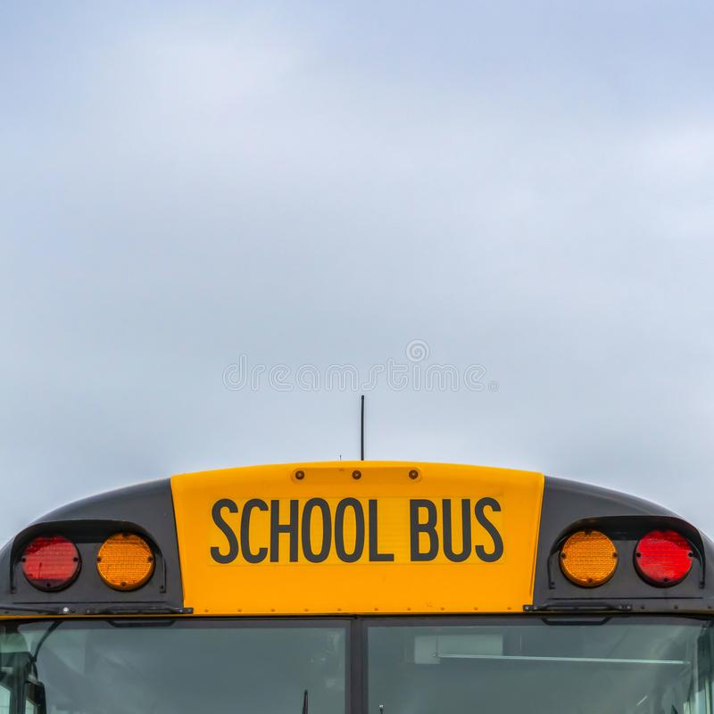 Square Front view of a yellow school bus with homes and cloudy sky in the background. Several side mirros and signal lights can be seen at the front of the stock photography