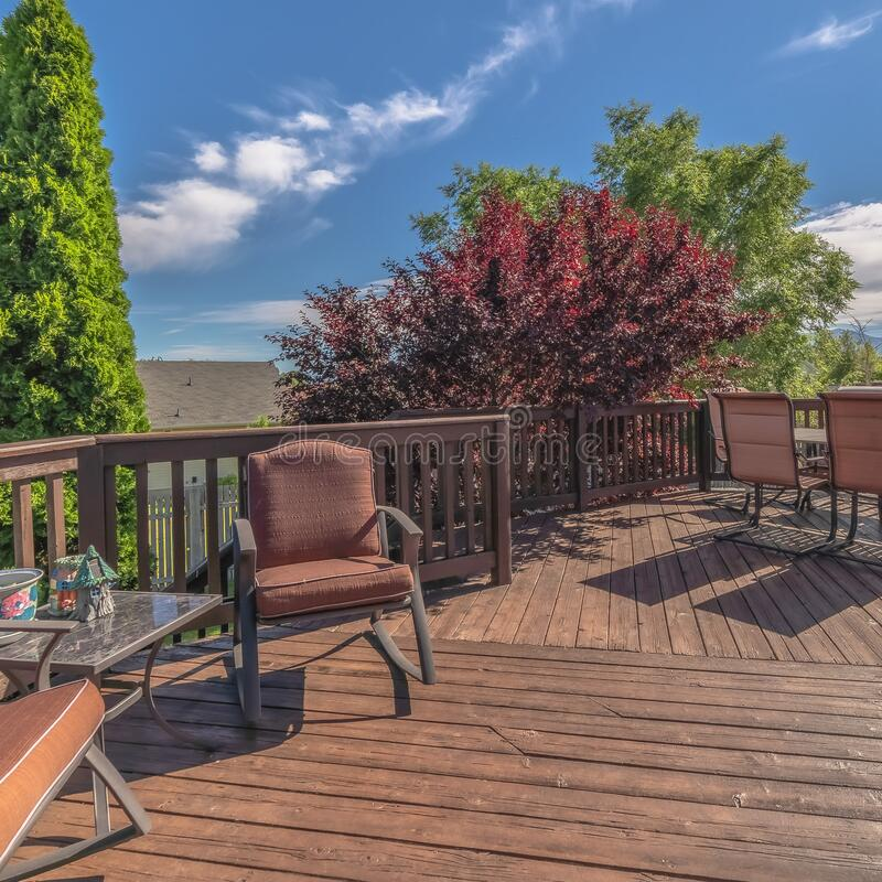 Square Furniture on the balcony of home with brown wooden floor railing and stairs. The outdoor living space has a scenic view of the yard, trees, and blue sky stock photos
