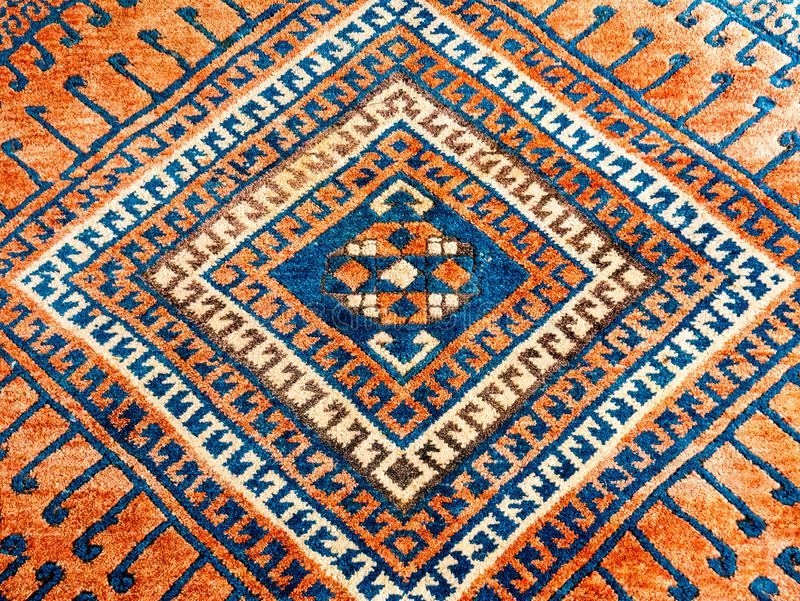 Square geometric pattern of oriental persian carpet in mainly red and blue stock photography