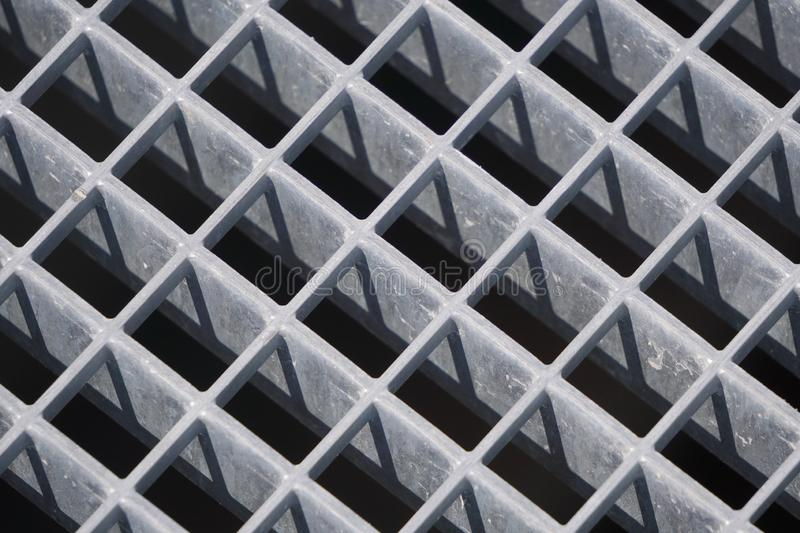 Square geometry of the iron plates, sturdy bars. play of light and shadow, screensaver, background. diagonal lattice background stock photography