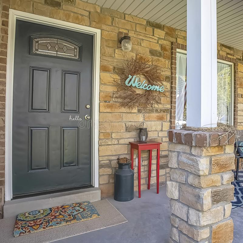 Square Glass paned front door and stone brick exterior wall at the facade of a home. A seating area, Welcome wreath, and ornaments can be seen on the small royalty free stock image