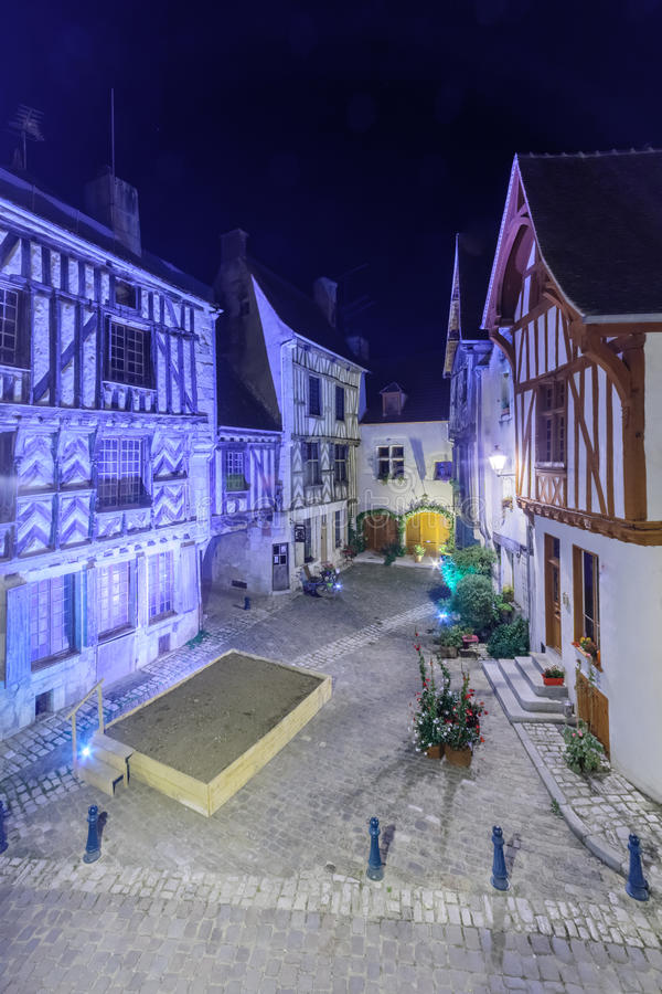 Square with half-timbered houses, in the medieval village Noyers-sur-Serein. Night view of a square place de la petite etape aux vins, with half-timbered houses royalty free stock photography