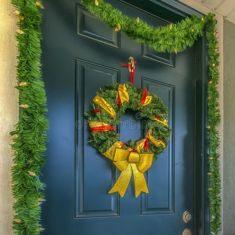 Square Home with a sunlit porch and front door decorated with wreath and garland. The scenic mountain and vibrant blue sky are reflected on the sliding glass stock images