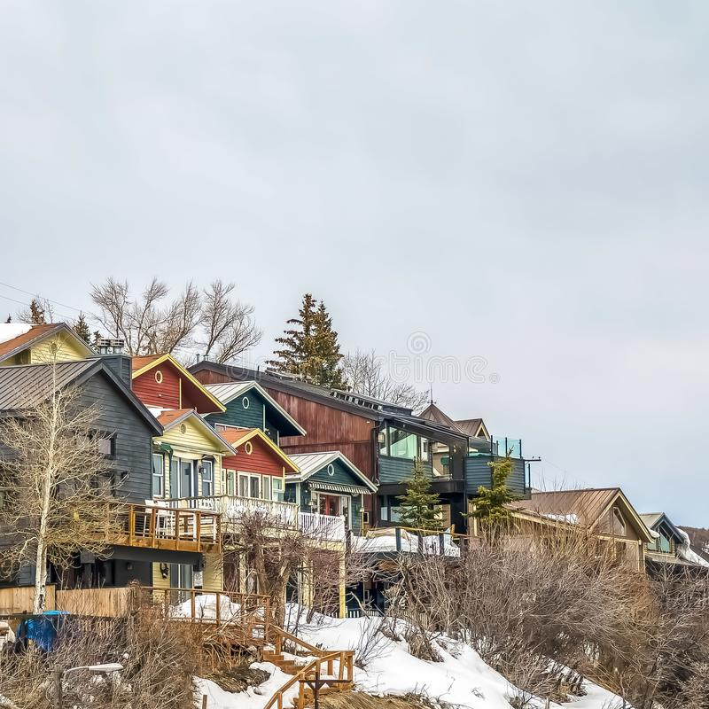 Square Homes with balconies on a mountain against sky filled with clouds in winter. Square frame Homes with balconies on a mountain against sky filled with stock photo