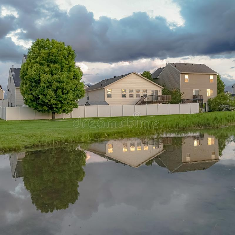 Square Homes and trees reflected on the shiny water of a pond amid a grassy terrain. Over the landscape is a bright sky with puffy gray clouds royalty free stock photography