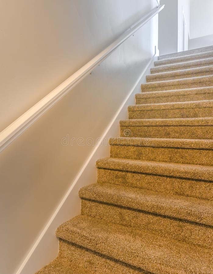 Square Interior of a house with a staircase covered with brown carpet stock photo