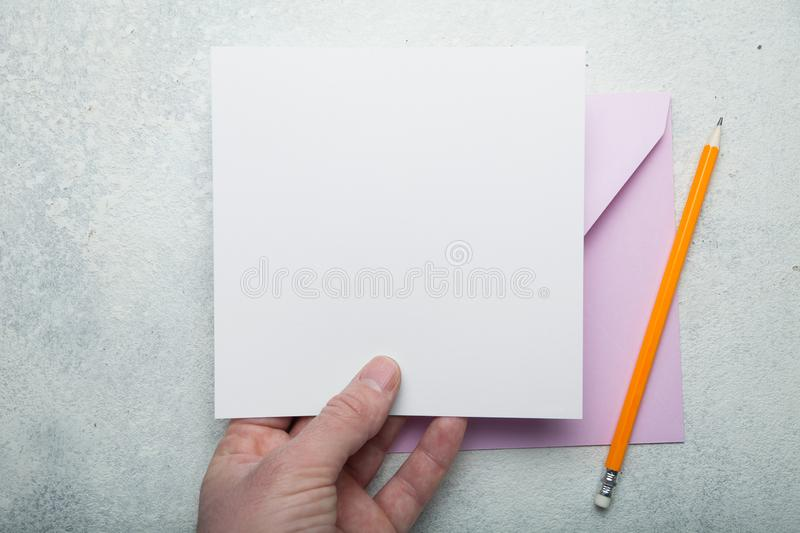 A square layout of paper and a pink envelope in his hand.  royalty free stock photo