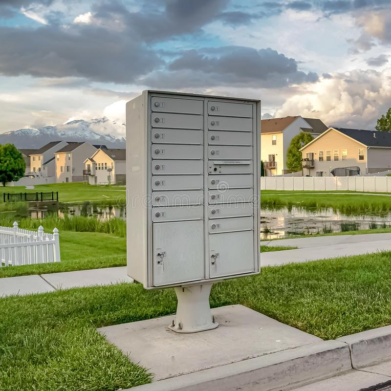 Square Mailbox on the side of the road with pond grassy terrain and homes background. Snow capped mountain and cloudy sky can also be seen in this landscape stock photo