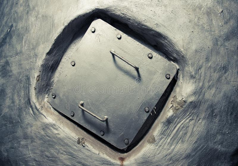 Square manhole cover inside wall stock photography