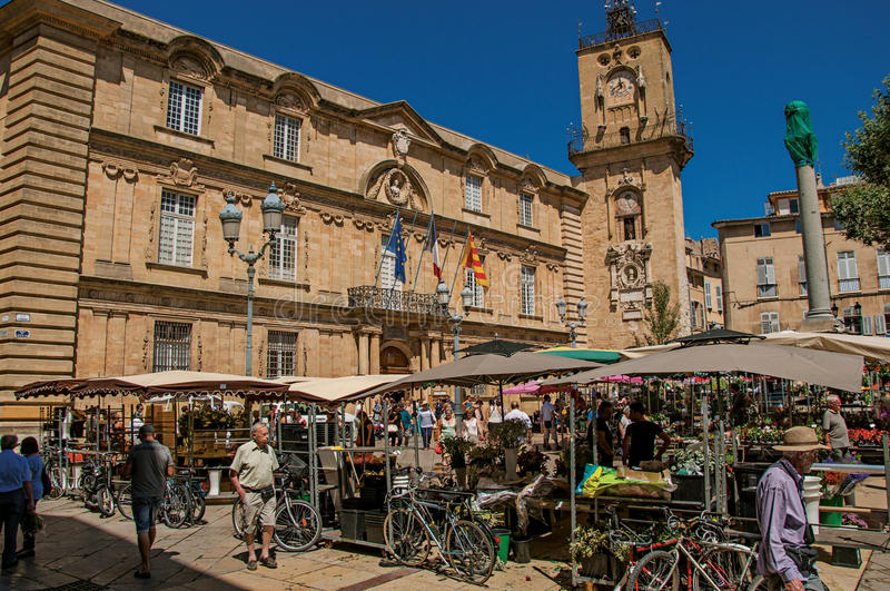 Square with market stall, people and clock tower in Aix-en-Provence, stock photography