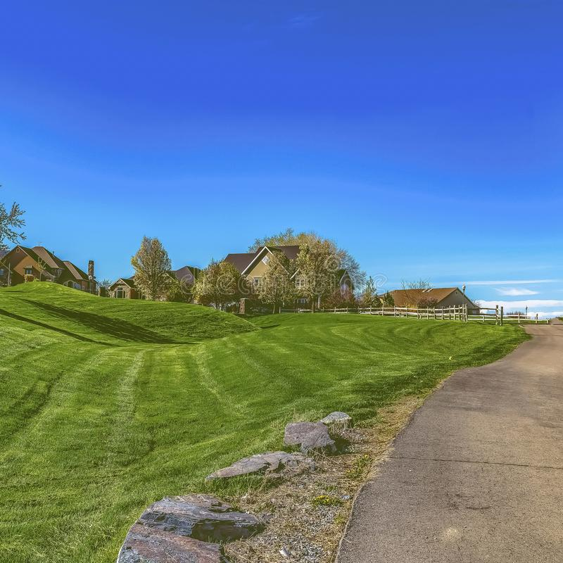 Square Narrow paved road on a vast grassy terrain under blue sky on a sunny day. The pathway leads to the houses on a residential area in the distance royalty free stock images