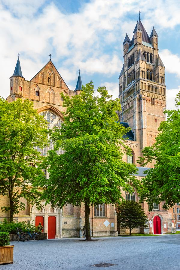 Square ner Saint Saviour`s Cathedral in Bruges. Square near Saint Saviour`s Cathedral, tower above green trees in Bruges Brugge old town, Belgium stock photos