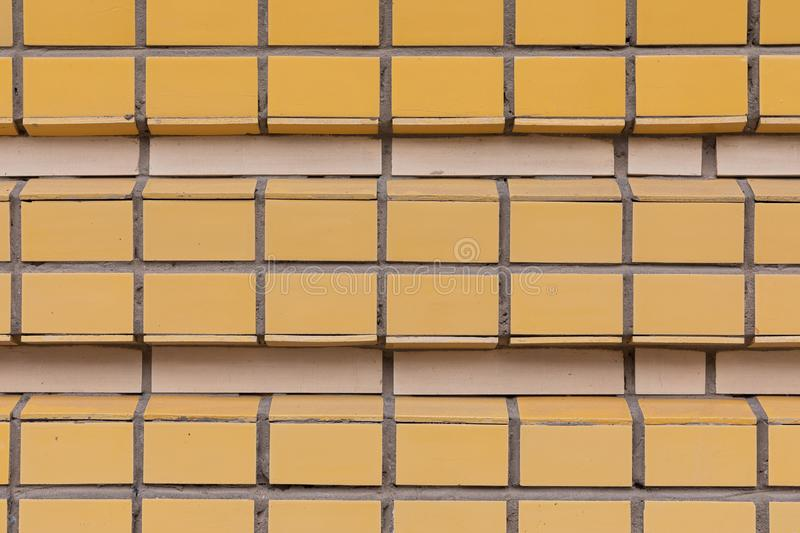 Square Orange and beige ceramic tile pasted in row on wall horizontal photo background. Square Wide Orange and thin beige textured tile pasted in row on wall stock image