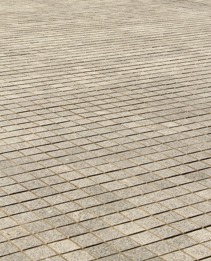 Square patterned paving. Grey square patterned paving outdoors showing texture and detail portrait orientation with copy space royalty free stock photos