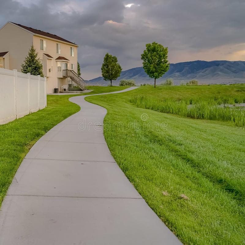 Square Paved walkway in front of homes with view of a pond and vast grassy terrain. A distant mountain can be seen against the sky filled with grasy clouds royalty free stock image