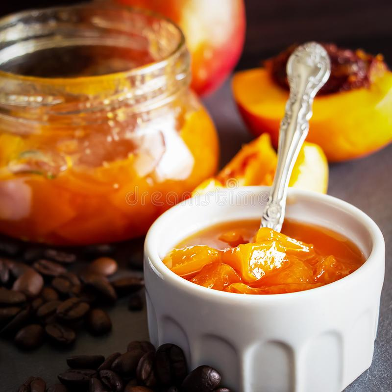 Square photo. Nectarine marmalade in white ramekin and jar with coffee beans. Dark background. Selective focus. Close up. Square photo. Nectarine marmalade in stock photography