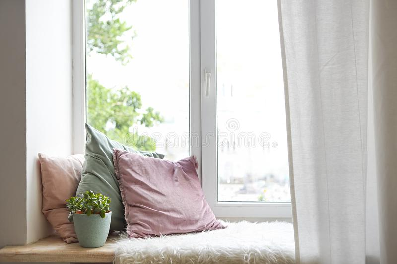 Square pillows, plaid and plant at the window stock images