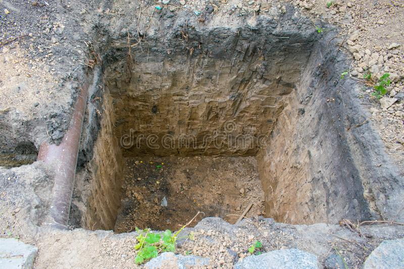 Square pit in the ground. Individual Home Sewage. Preparation for sewer pipes installation royalty free stock photo
