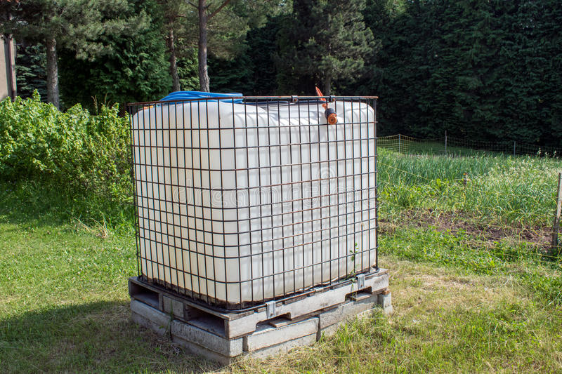 Square plastic water tank in the garden.rainwater recuperator baril.  royalty free stock photography