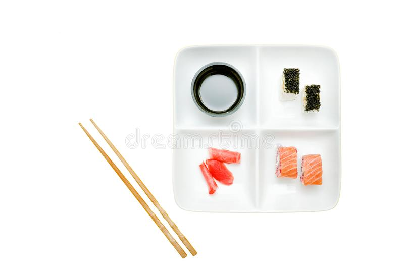 Square plate with rolls and sushi. Soy sauce, ginger and chopsticks. Food concept. Isolated. White background royalty free stock photo