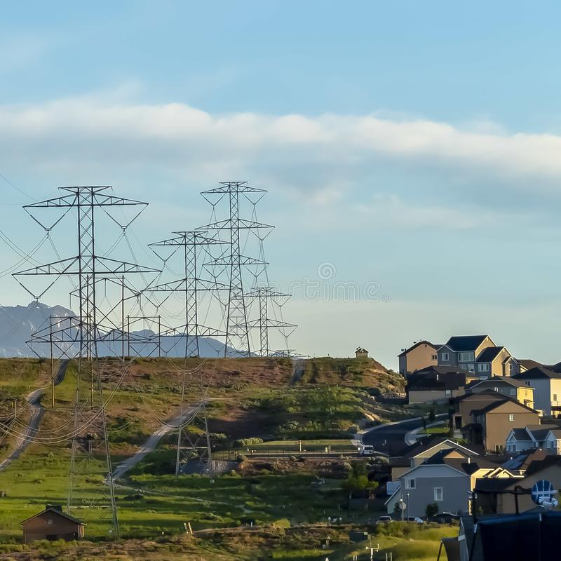 Square Power lines towering over neighborhood and roads in the valley on a sunny day. Blue sky and mountain with snowy peaks cna be seen in the background royalty free stock image