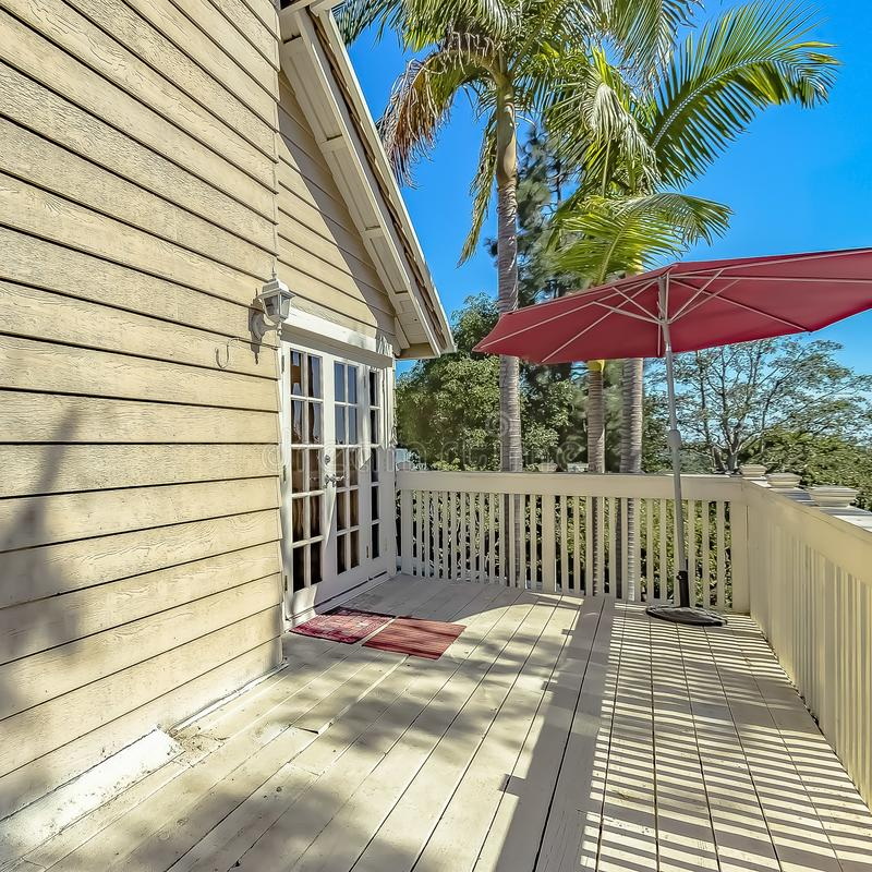 Square Red umbrella at the corner of the balcony of a house with wooden exterior wall. Lush trees can be seen against the clear blue sky on this sunny day royalty free stock images