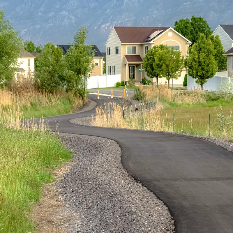 Square Road winding amid grassy terrain with homes trees and mountain in the distance. Traffic delineator posts are placed in the middle and sides of the road royalty free stock photography