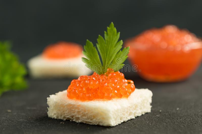 Square shaped sandwich with red caviar on black background stock images