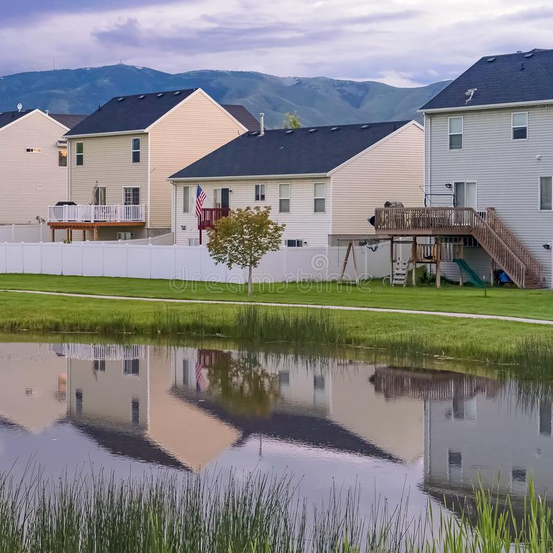 Square Shiny pond and pathway amid a grassy terrain in front of homes with balconies. A mountain and cloudy sky can be seen in the background stock images