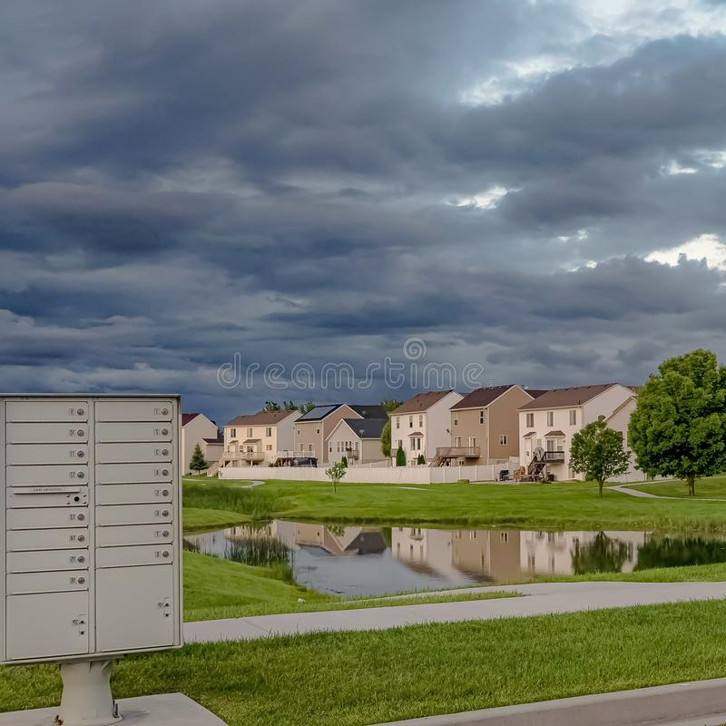 Square Sky filled with gray clouds over homes and pond amid a vast grassy terrain. White metal cluster mailbox at the side of a road can be seen in the royalty free stock photo