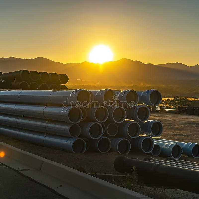 Square Stack of pipes with a golden sun setting behind a mountain in the background stock images